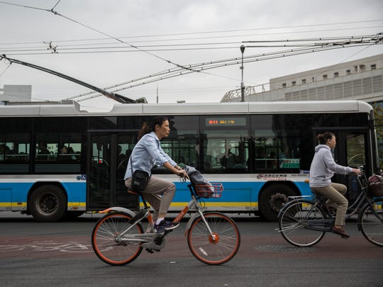 A woman rides a rental bike through an intersection on Wednesday, Sept. 27, 2017, in Beijing. Bikes and scooters have become a popular means of transportation in the large city where car traffic is always heavy.