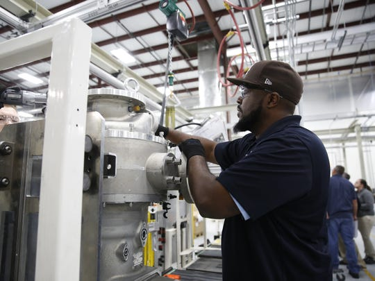 Production Technician Delvin Peoples works on assembling a compressor at the Danfoss Turbocor manufacturing facility Wednesday.