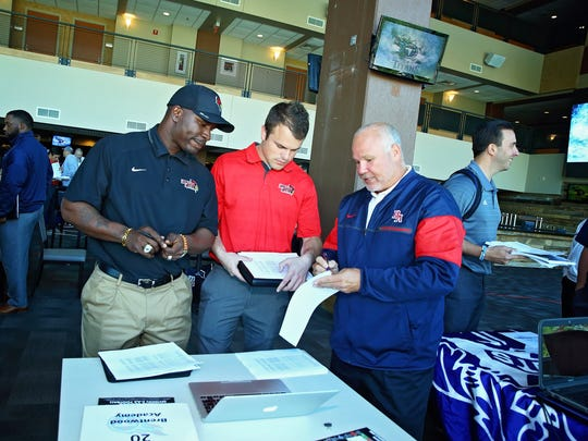 Brentwood Academy assistant coach Buddy Alexander talks to two assistant coaches from Illinois State University at the Tennessee Titans high school recruiting fair. The fair started in 2015 to give unsigned high school players a chance to continue their football careers in college.