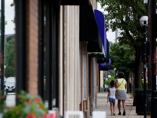 Pedestrians walk down Hamilton Avenue, Tuesday, June