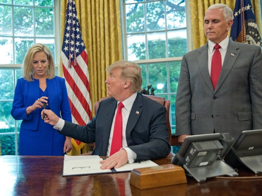 President Donald Trump gives the pen he used to sign the executive order to end family separations to Homeland Security Secretary Kirstjen Nielsen.