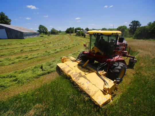 Justin Dammann cuts hay in a field on a Page County