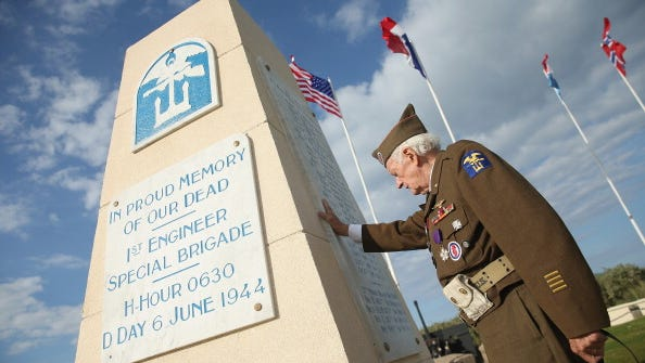 Veteran Frederick Carrier, 89, who served in the 1st Engineer Special Brigade of the U.S. Army and landed at Utah Beach on D-Day, prays for the 171 men of his unit who died at a monument to them on June 5, 2014 at Utah Beach, France. Carrier says he designed the monument, which sits on top of a former German bunker, and built it with the help of 12 German prisoners of war in October, 1944, and that he hid three bottles of Calvados inside.