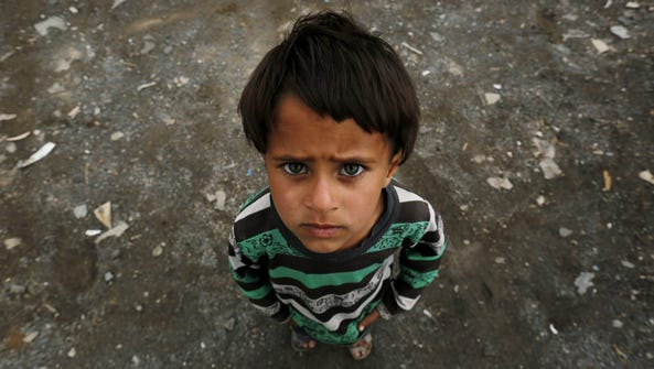 A boy poses for a picture outside his family house