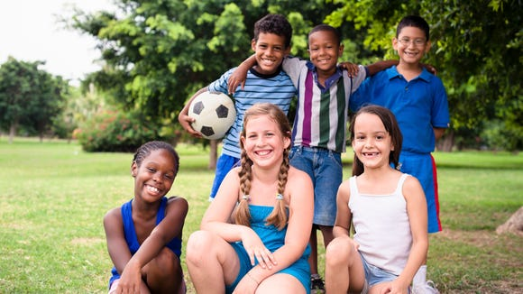 Smiling culturally-diverse group of children on soccer field