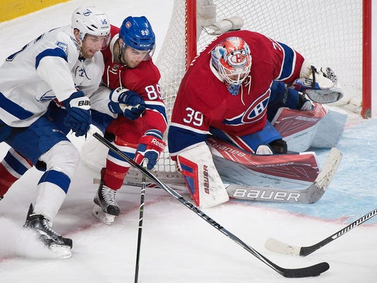 Tampa Bay Lightning's Braydon Coburn (55) moves in on Montreal Canadiens goaltender Mike Condon as Canadiens' Ryan Johnston (89) defends during second-period NHL hockey game action in Montreal, Saturday, April 9, 2016. (Graham Hughes/The Canadian Press via AP) MANDATORY CREDIT