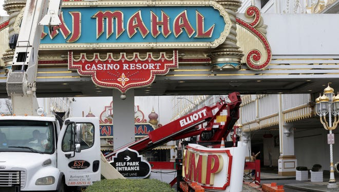 Workers remove the Trump name from the sign at the entrance of the former Trump Taj Mahal casino in Atlantic City.
