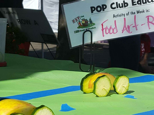 Kids race apple and zucchini cars as a part of the POP Kids Club, a kids program designed to introduce kids to healthy eating habits.