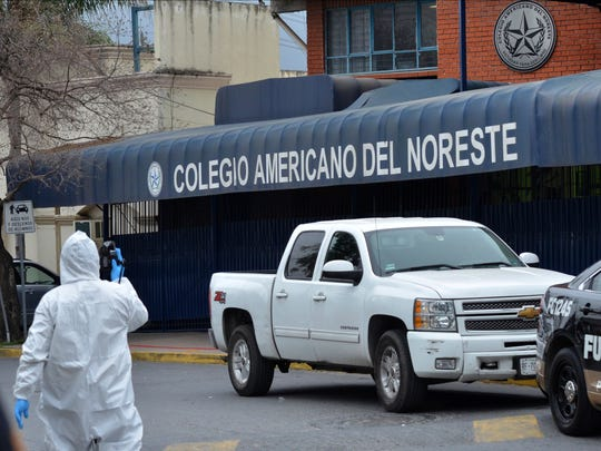 A forensic investigator walks outside a private school in Monterrey, Mexico, Wednesday, Jan. 18, 2016. A 15-year-old student opened fire with a gun at the school, hitting a teacher and two other students in the head before killing himself.