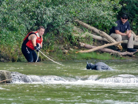 A diver searches a section of the Winooski river below
