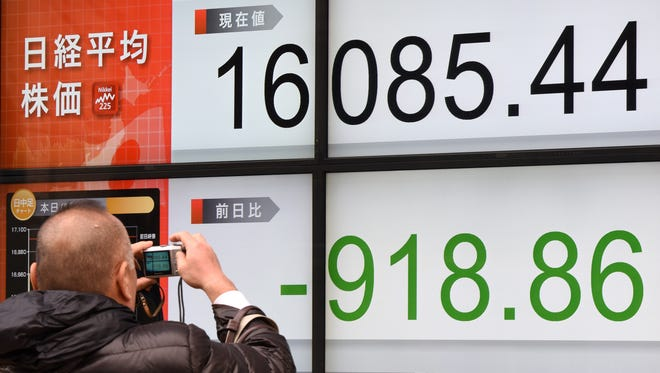 A man takes pictures of an electric quotation board flashing Nikkei 225 index prices in Tokyo on Feb. 9.