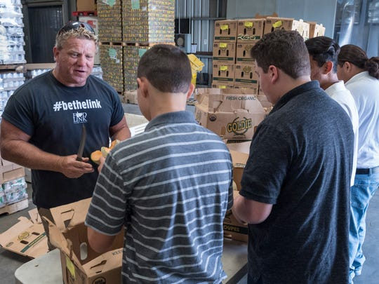 Greg Brisco, left, works with students from Courage to Change culling cantaloupes for distribution at Food Link in Exeter on Monday, August 20, 2018.