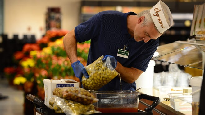 The olive bar is getting filled at Wegmans, which is opening its first store in Bergen County on Sunday morning. Venders and staff are stocking the shelves to get the store ready for the grand opening.