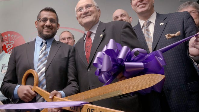 In his last official act as mayor, Al Haidous helps cut the ceremonial ribbon at the new Urgent Care medical facility with owner Nabeel Shahid and State Rep. Robert Kosowski, D-Westland.