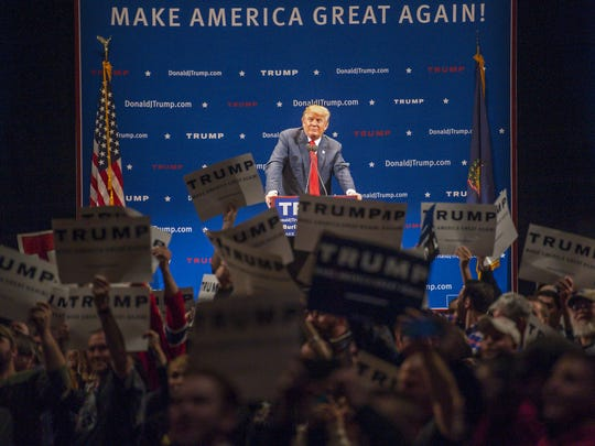 Republican presidential candidate Donald Trump looks on as protesters are removed during his speech at the Flynn Theater in Burlington on Thursday.
