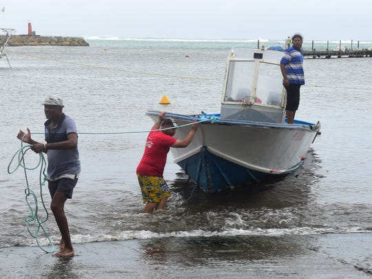 Men remove a boat from the water ahead of Hurricane Maria in the Galbas area of Sainte-Anne on the French Caribbean island of Guadeloupe, early Monday, Sept. 18, 2017. Hurricane Maria grew into a Category 3 storm on Monday as it barreled toward a potentially devastating collision with islands in the eastern Caribbean. (AP Photo/Dominique Chomereau-Lamotte)