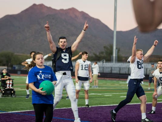 Penn State quarterback Trace McSorley celebrates a catch by Olivia Baumgardner, 10 of Arcadia, Calif., during a charity kickball event with the Children's Cancer Network and HopeKids on Wednesday, Dec. 27, 2017, in Scottsdale, Ariz. Penn State plays Washington in the Fiesta Bowl on Saturday. (Joe Hermitt/PennLive.com via AP)