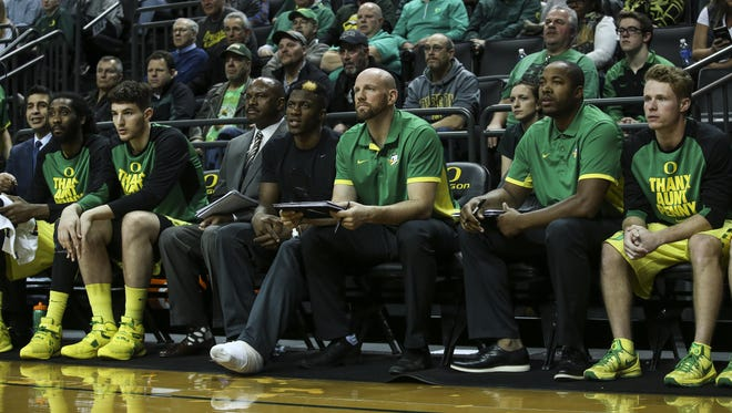 Oregon undergraduate assistant coach Freddie Jones (second from right) watches action from the bench during a game this season.