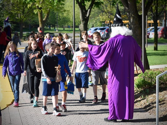 Students smile at John Augustin in his wizard costume as they arrive Wednesday, May 18, 2016, for the Young Authors/Young Artists Conference at the College of St. Benedict.