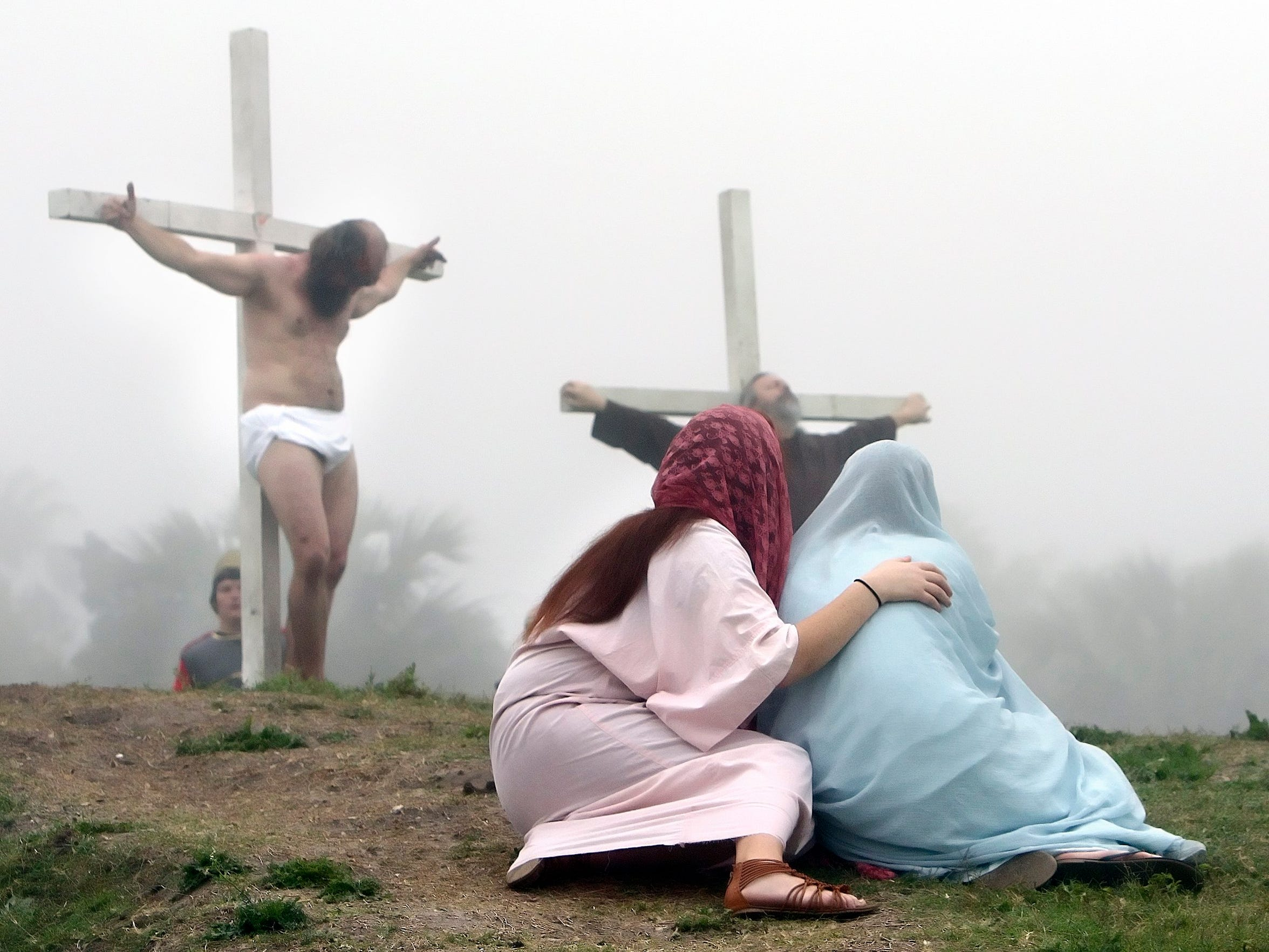 Kiki Pena (left) as Mary Magdalene and Nastassia Abshire as Mary the mother of Jesus sit at the foot of the cross as Jesus, portrayed by Max Moorman, hangs on the cross in March 2016 at Cole Park in Corpus Christi.