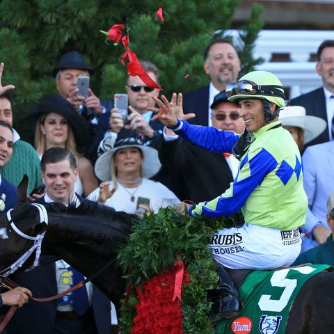 Jockey John Velazquez throws roses atop Always...