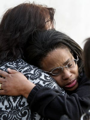A relative comforts Sheryl Jones, mother of Wayne State University law student Tiane Brown, during a candlelight vigil for her daughter at Wayne State University in Detroit on Wednesday, Oct. 30, 2013.