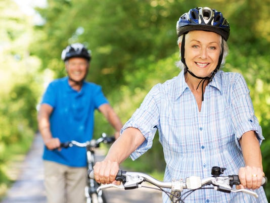 Happy Senior Woman With Man Riding Bicycles.