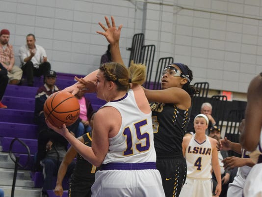 LSU at Alexandria's Taylor Holzmeier (15, left) looks to get two against Jarvis Christian College's Briauna Williams (15, right) Thursday.