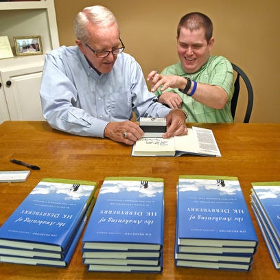 HK Derryberry, right, signs books that his friend and