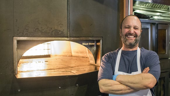 Chef Peter Affatato stands next to the wood-fired oven