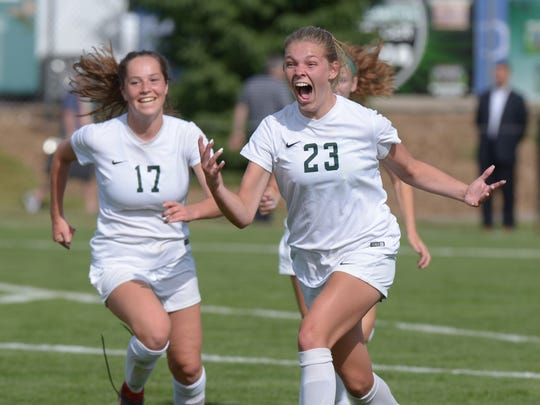 Riley Schultz (23) and Michelle Jecmen celebrate as the buzzer sounds with Novi claiming the Div. 1 state soccer title with a 1-0 victory over Grand Blanc on June 15 at Williamston High School.