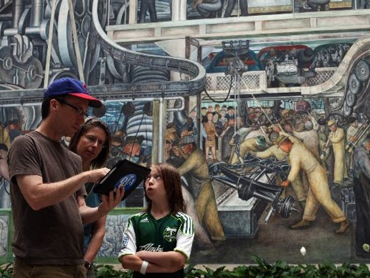 Brian Martin, left, Karen Martinek and Emma Martin of Portland, Ore., use an interactive device to learn about the Diego Rivera mural at the Detroit Institute of Arts in Detroit on July 19, 2012. They have Detroit roots and are