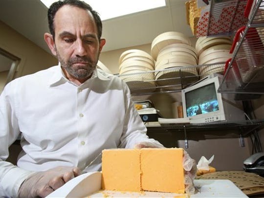 Ken Monteleone, owner of Fromagination, slices a block