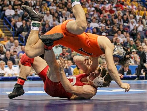 Illinois' Isaiah Martinez, top, wrestles with Cornell's Brian Realbuto during their 157-pound championship match Saturday, March 21, 2015, at the NCAA Division I Wrestling Championships in St. Louis. Martinez beat Realbuto 10-2 to take the national championship.(AP Photo/Tom Gannam)