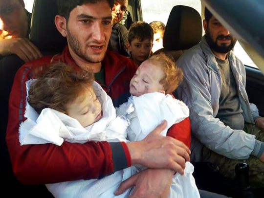 In this picture taken on Tuesday April 4, 2017, SAbdul-Hamid Alyousef, 29, holds his twin babies who were killed during a suspected chemical weapons attack, in Khan Sheikhoun in the northern province of Idlib, Syria. Alyousef also lost his wife, two brothers, nephews and many other family members in the attack that claimed scores of his relatives. The death toll from a suspected chemical attack on a northern Syrian town rose to 72 on Wednesday as activists and rescue workers found more terrified survivors hiding in shelters near the site of the harrowing assault, one of the deadliest in Syria's civil war.
