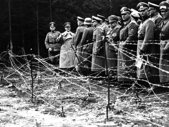 "FILE- In this Oct. 6, 1938, file photo, Adolf Hitler, second from left, stands in front of the barbed wire fortifications at Kreuzbuche, Germany after German troops advanced and occupied the second zone of Sudetenland. The book, ""Human Rights After Hitler"" by British academic Dan Plesch, says Hitler was put on the United Nations War Crimes Commission's first list of war criminals in December 1944, but only after extensive debate and formal charges brought by Czechoslovakia. Plesch, who led the campaign for open access to the commission's archive, told The Associated Press on Tuesday, April 18, 2017, that the documents show ""the allies were prepared to indict Hitler as head of state, and this overturns a large part of what we thought we knew about him."""