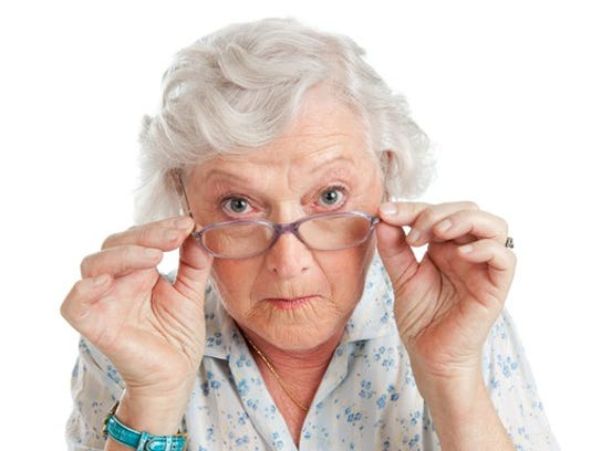 A white haired woman peering with interest over her glasses.