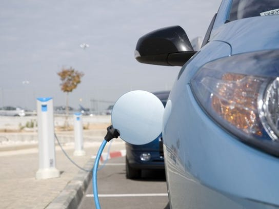 An electric car getting a fill-up of electricity.
