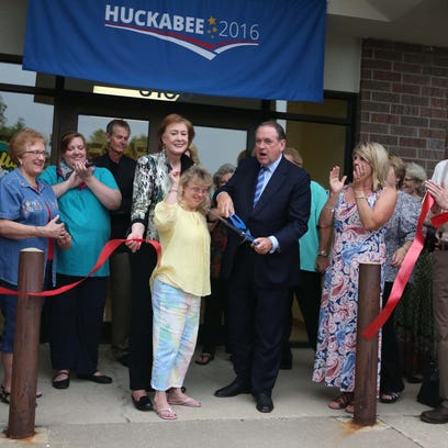 on Tuesday, June 30, 2015 in Urbandale. Mike Huckabee, with the help of his wife Janet and Wendy Davis, a campaign volunteer cut the ribbon to officially open Huckabee's Iowa campaign office on Tuesday, June 30, 2015 in Urbandale.