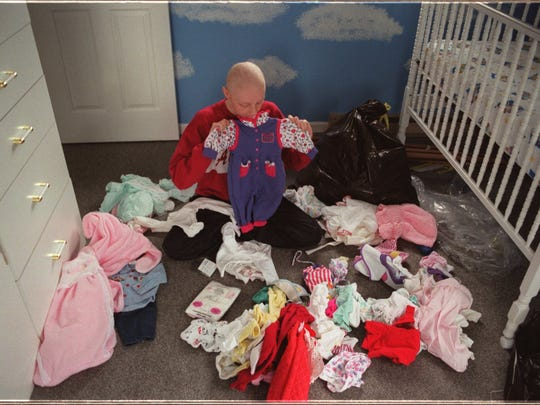 Pullins Sorts through the piles of baby clothing for