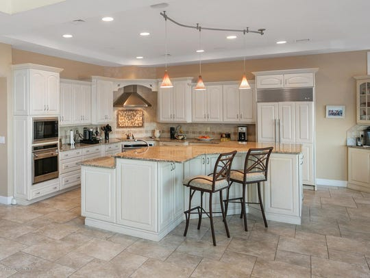 The massive kitchen features a huge granite stone center
