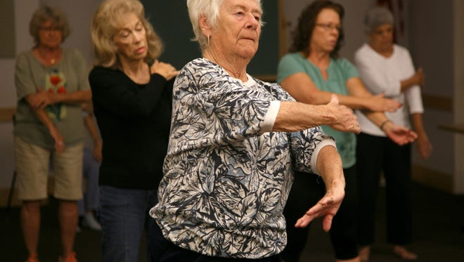 Students in a tai chi class work through the movements of the exercise in the community room at the Santa Clara branch of the Washington County Library Saturday, Oct. 24, 2015.