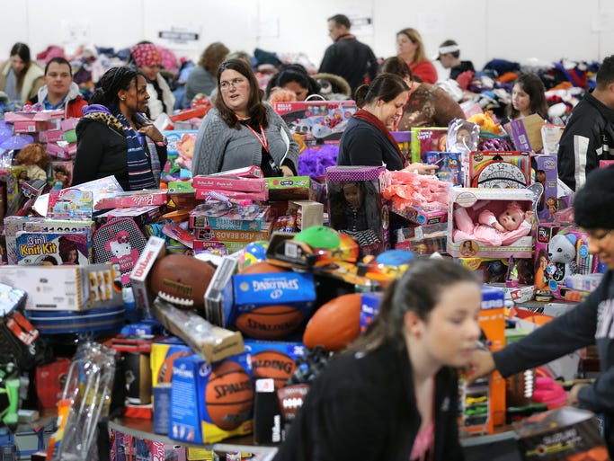 Volunteers help recipients walk through and grab what they need during the annual Christmas Giveaway at the Hamilton County Fairgrounds on Saturday, December 15, 2013. Good Samaritan of Hamilton County held its annual Christmas Giveaway where 7,000 pre-qualified needy families in Hamilton County got the opportunity to pick clothes, food, toys and other things that will help them have a nice holiday season for them and their families.