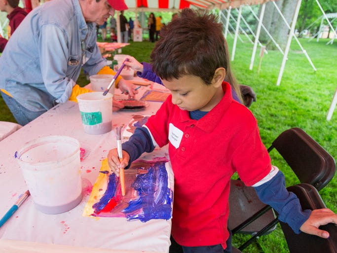Deshawn Spangler, 7, Indianapolis, paints at Arts for All Fest sponsored by VSA Indiana for about 300 kids with disabilities at the governor's mansion, Indianapolis, Wednesday, May 14, 2014.