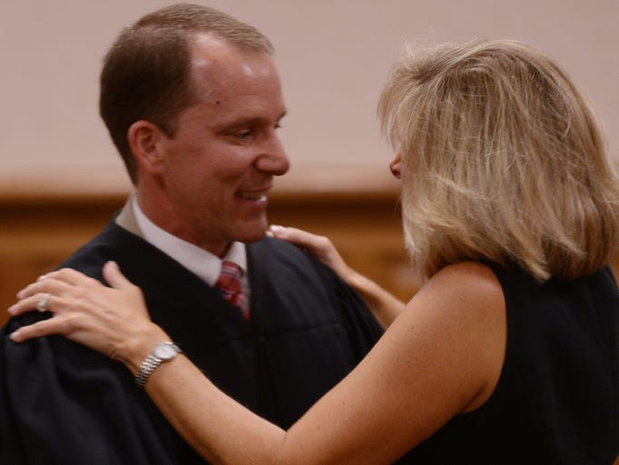 Kyle Atkins (left) and his wife, Elizabeth Atkins, (right), hug after he was sworn in Thursday afternoon at the Madison County CJC. Atkins was elected as the new District III Circuit Court Judge and will officially take office on Sept. 1.