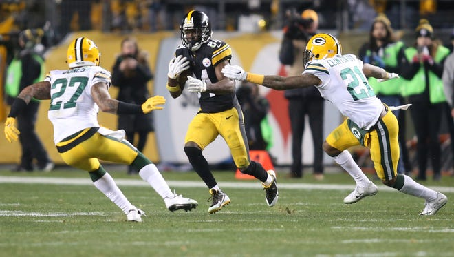 Pittsburgh Steelers wide receiver Antonio Brown (84) runs after a catch as Green Bay Packers strong safety Josh Jones (27) and free safety Ha Ha Clinton-Dix (21) defend during the fourth quarter at Heinz Field.