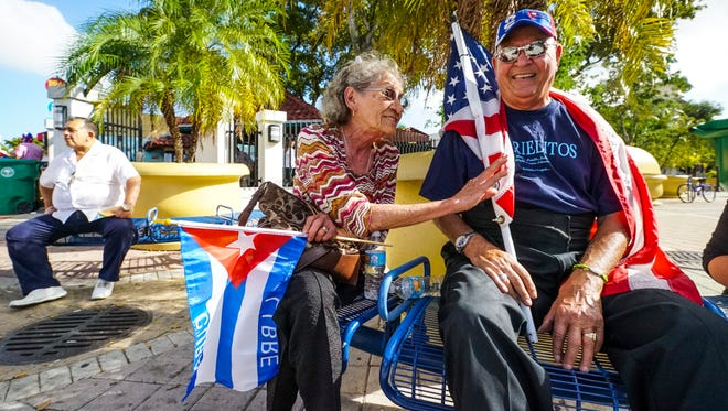 Dani Perez and his wife Silvia Preze sit with an American Flag and a Cuban flag as they wait for the celebration. Little Havana, Miami, was all a buzz as organizers prepared for the evening's events. The Bay of Pigs Veterans Association will hold a rally in Little Havana for Cuban freedom. These older Cuban exiles are dwindling, while the younger generation of Cubans are more lenient toward the Castro regime.