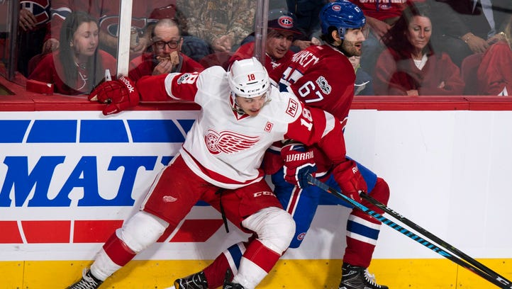 Detroit Red Wings' Robbie Russo (18) hangs on to Montreal Canadiens' Max Pacioretty (67) during the second period.