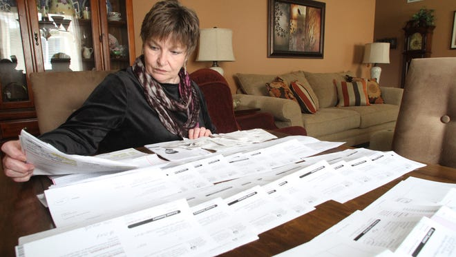 In this 2013 Livingston Daily file photo, Kathy Pugh reviews some of the medical bills she and her mother have received in the wake of treatment for fungal meningitis. Her mother, Evelyn Bates-March, died in February.