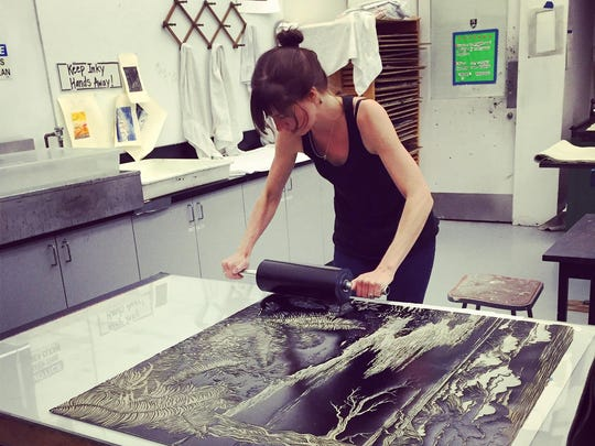 Portland printmaker Kelli MacConnell inks one of her linocuts to prepare it for printing.